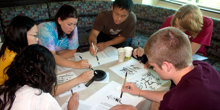 A group of students writing Chinese Calligraphy
