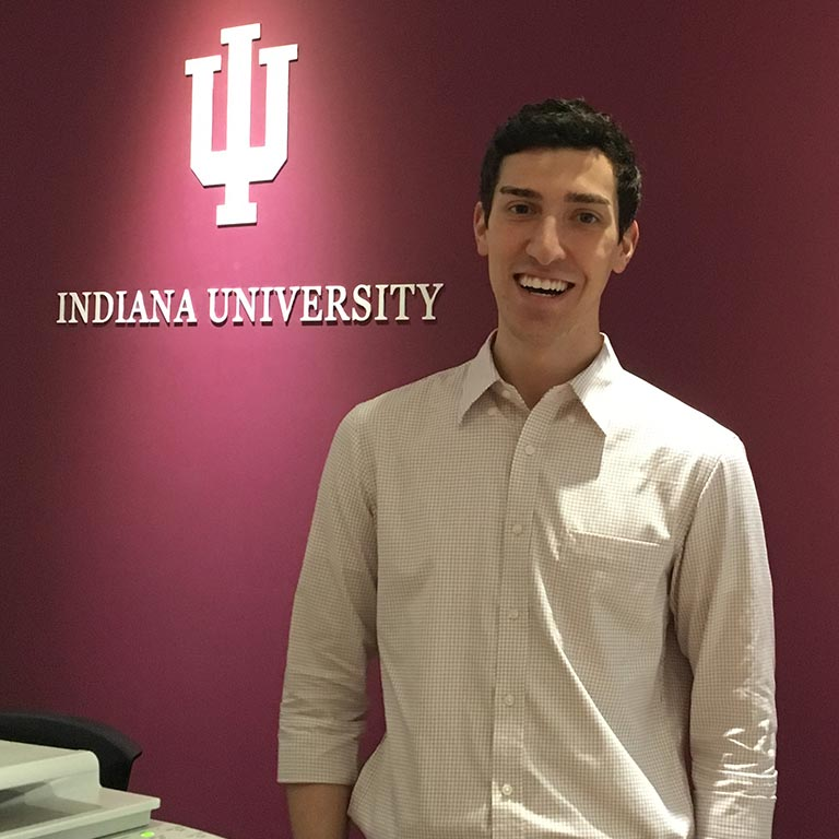 Student standing in front of Indiana University sign
